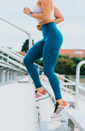 A woman running up steps wearing leggings and a smartwatch.