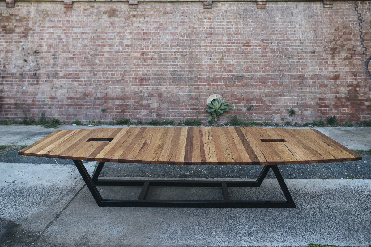 Navally inspired custom boardroom table built in alternating boards of recycled Ash and Blackbutt with a steel base. Designed by MMD Designs with Thor Diesendorf.