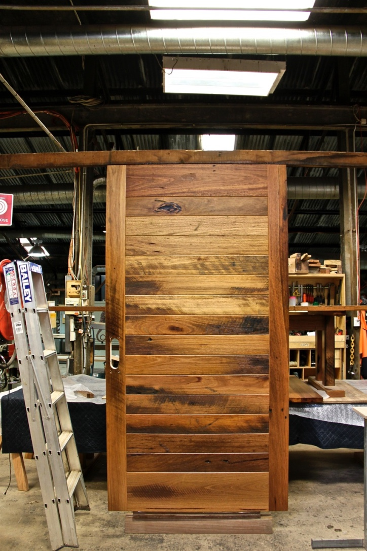 Horizontal tongue and groove entry door made from 40mm thick recycled hardwood for extra insulation and sound proofing. This door will keep the baddies out!