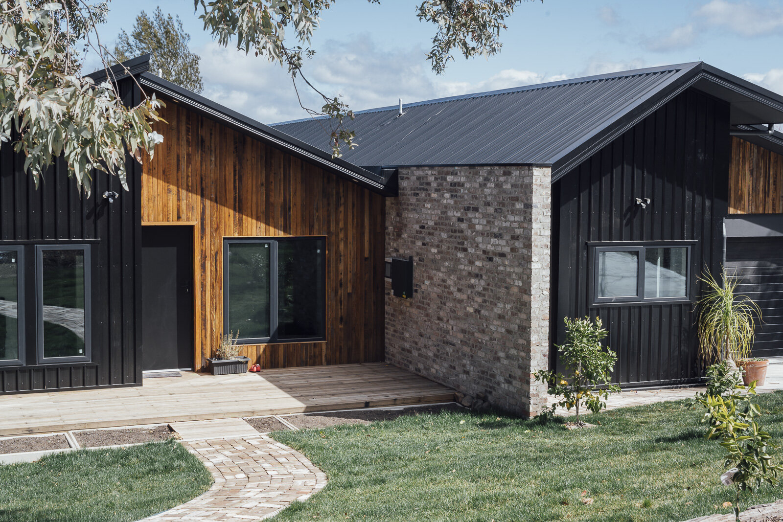 The black insulated panels, recycled Blackbutt cladding & decking, and double glazed windows.