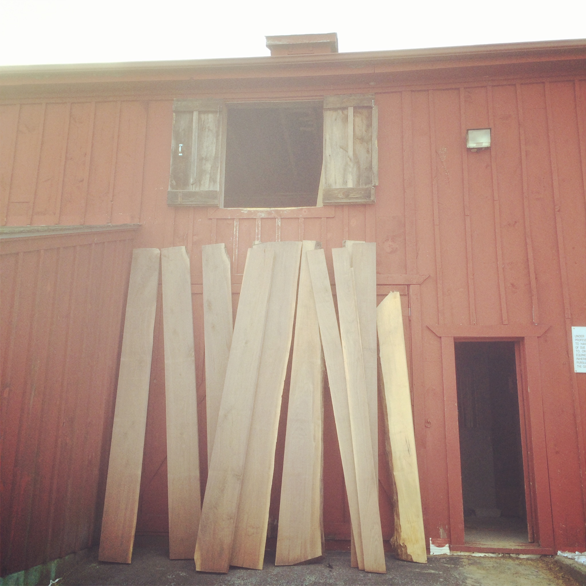 "The search always starts at the Sawmill for me. Here you can see a fairly large amount of Black Walnut, all of which is from Coventry RI. The barn door was made from two large boards on the far left. We resawed one of the boards down to 3/4"", which became the panel. The other board was ripped down the middle and cut into 4 separate sections to make the frame of the door."