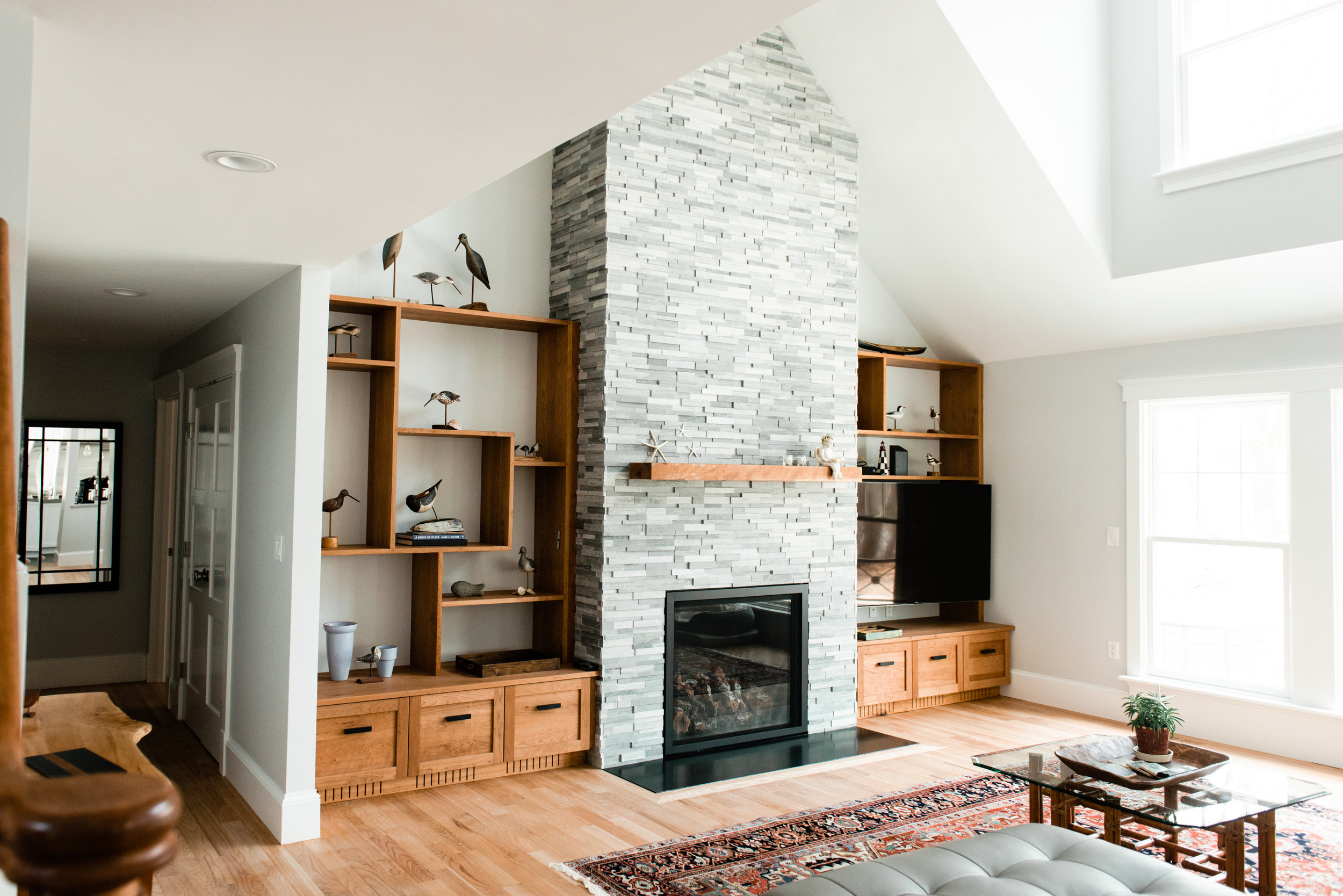 Cherry Shelves made with sliding dovetail construction. Light grey stone fireplace with solid cherry mantle.