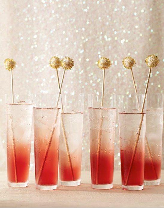 "We love these gold swizzle sticks that are featured in Martha Stewart's ""Homemade Holiday Crafts"" book. To create an ombre ""red carpet"" drink, take a red liqueur like PAMA pomogranate liqueut and pour it carefully in the bottom. Tip the glass and top it with sparkling water or champagne. Don't mix and let the red liqueur settle to the bottom and create an ombre effect."