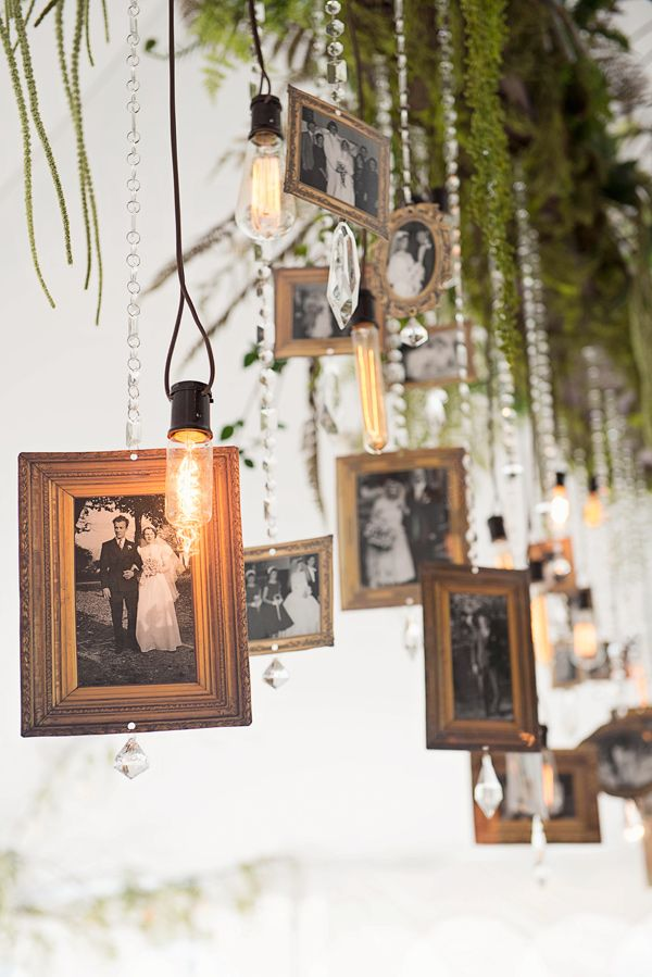This hanging display of photos with antique inspired light bulbs and crystals is pure genius to let people enjoy the pics all night long!