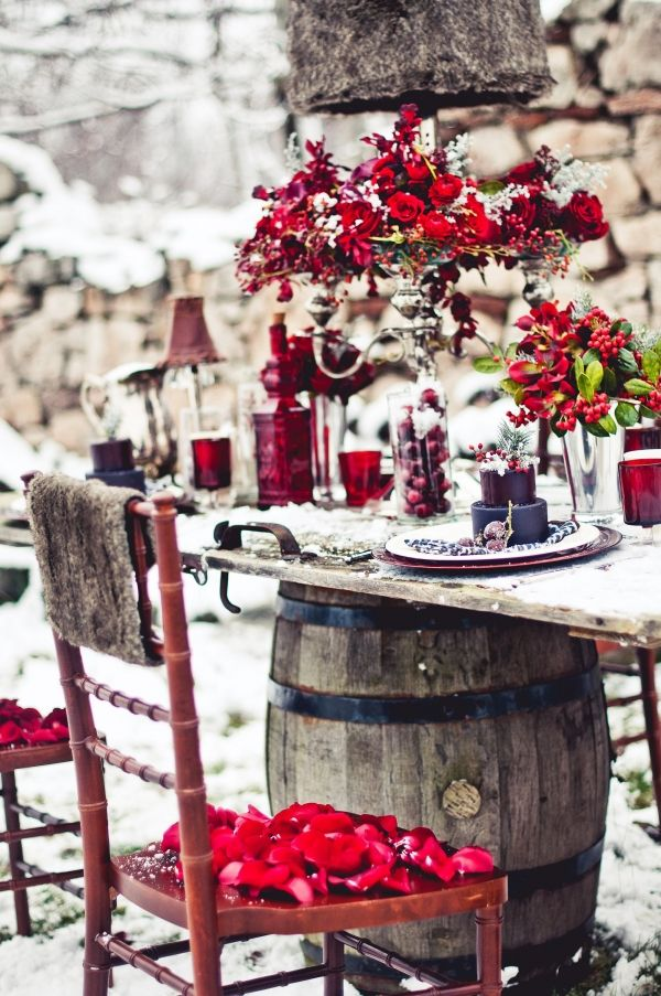 This winter red tablescape is so dramatic and so perfect! We love the repurposed door as the table and the fur accent on the chair and the lamp.
