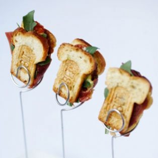 "I'm not sure what's cuter - the little ""BLT"" branding on the toast of these mini BLT's or the little wire holders? Either way, we think these would be a hit!"