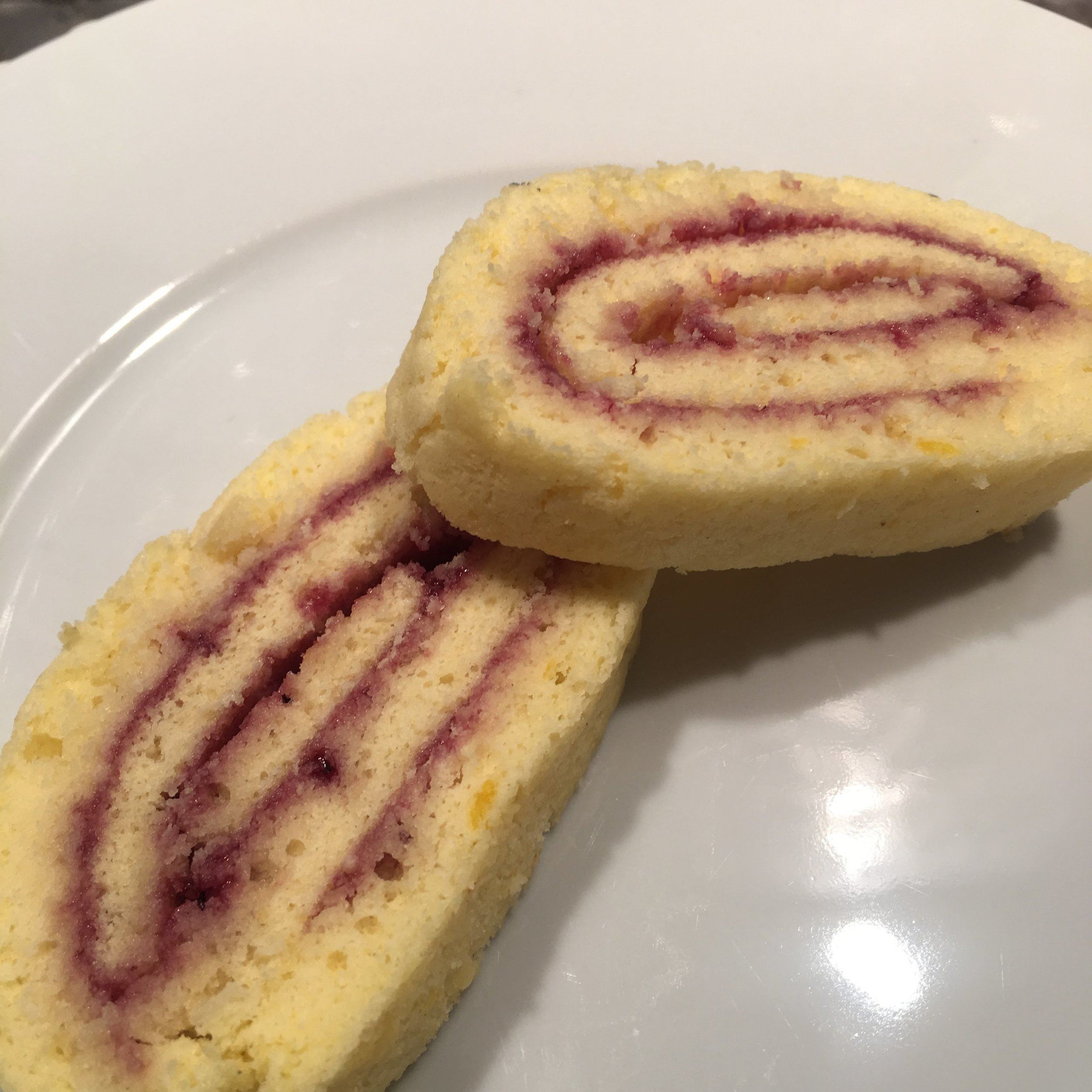 Slices of Boston Strong Jelly Roll filled with a mixture of strained blueberry preserves and strawberry jelly.