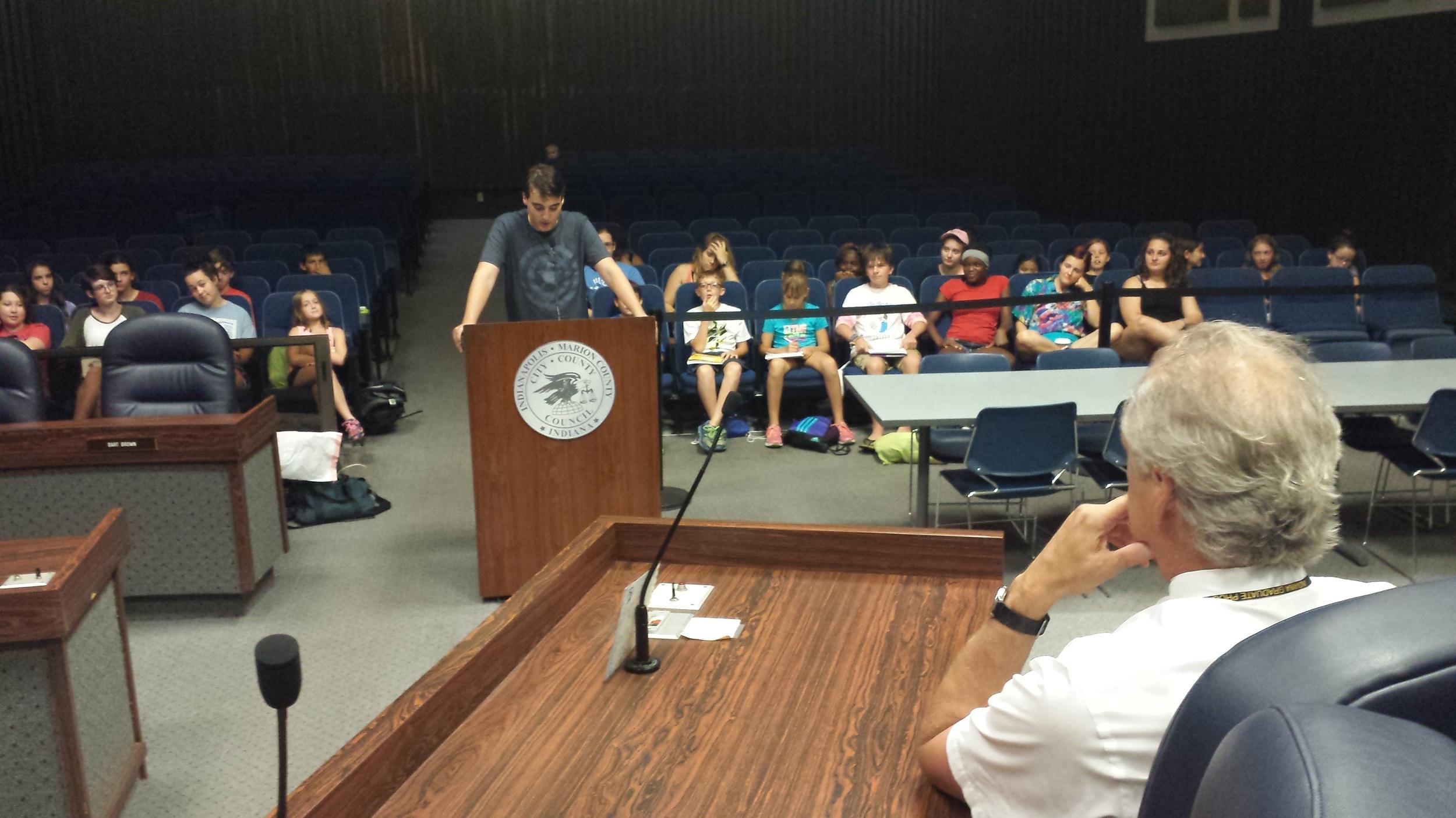 Ben, 15, from International School of Indiana, testifies to, in the foreground, Judge David Dreyer.