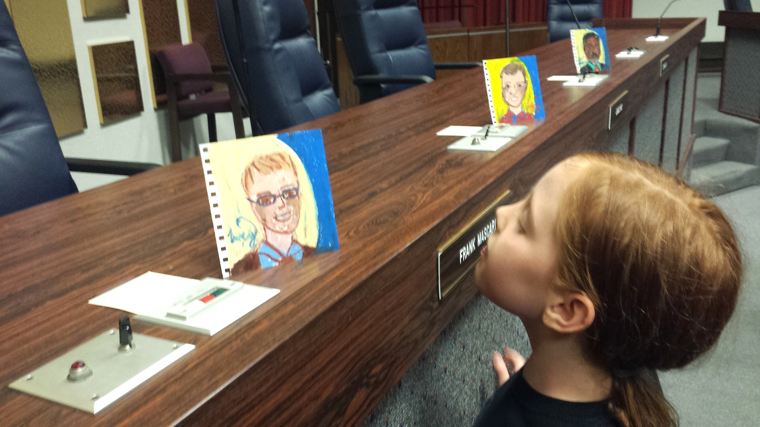 Ella, a student at School 91, inspects Lucy's portrait work.