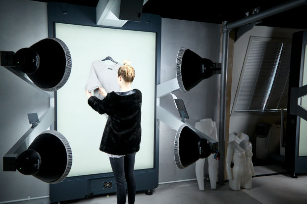 A stylist using one of Boohoo's several StyleShoots Vertical machines in their Manchester, UK HQ