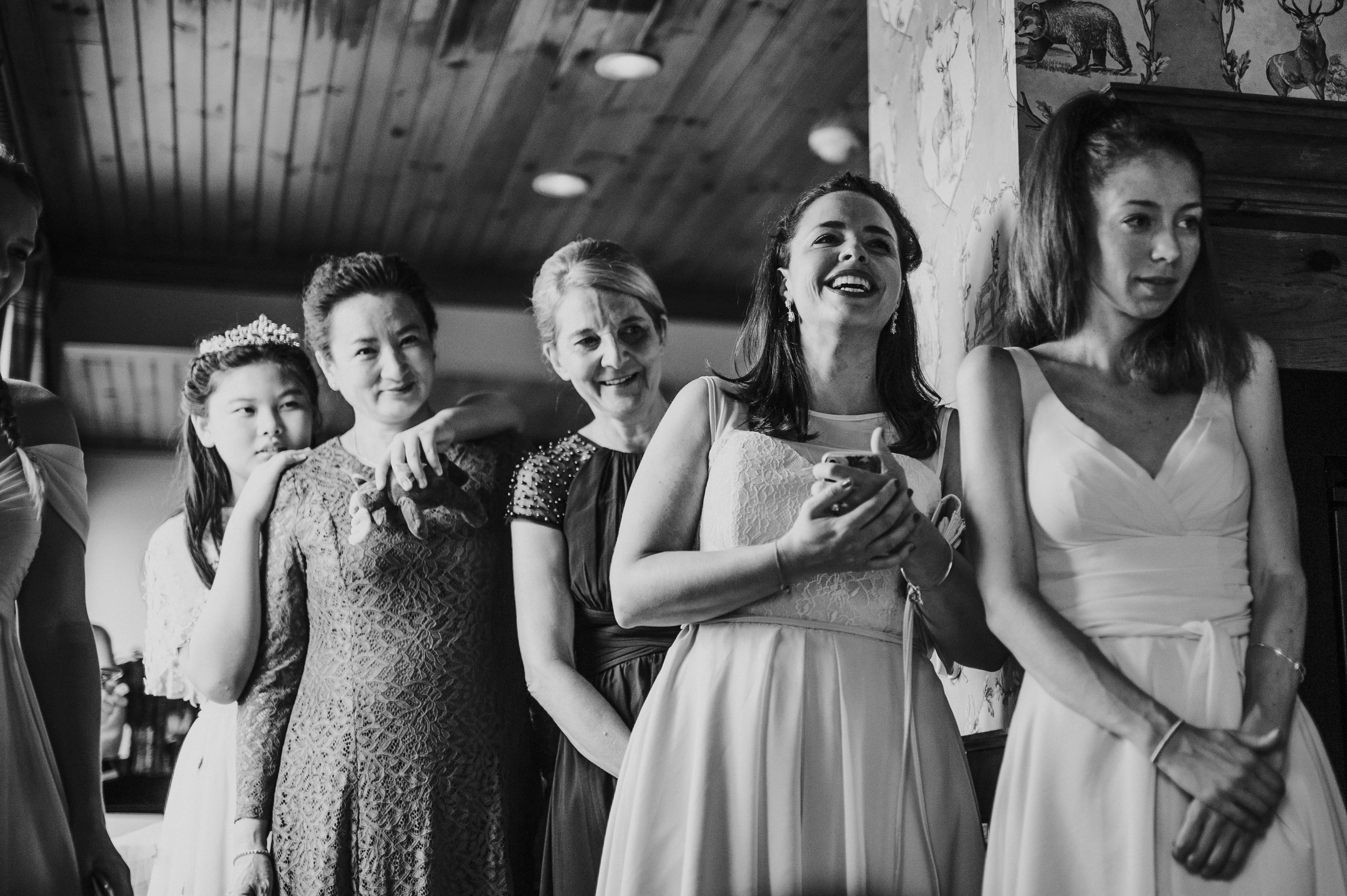 Wedding party reaction to bride opening gift from groom