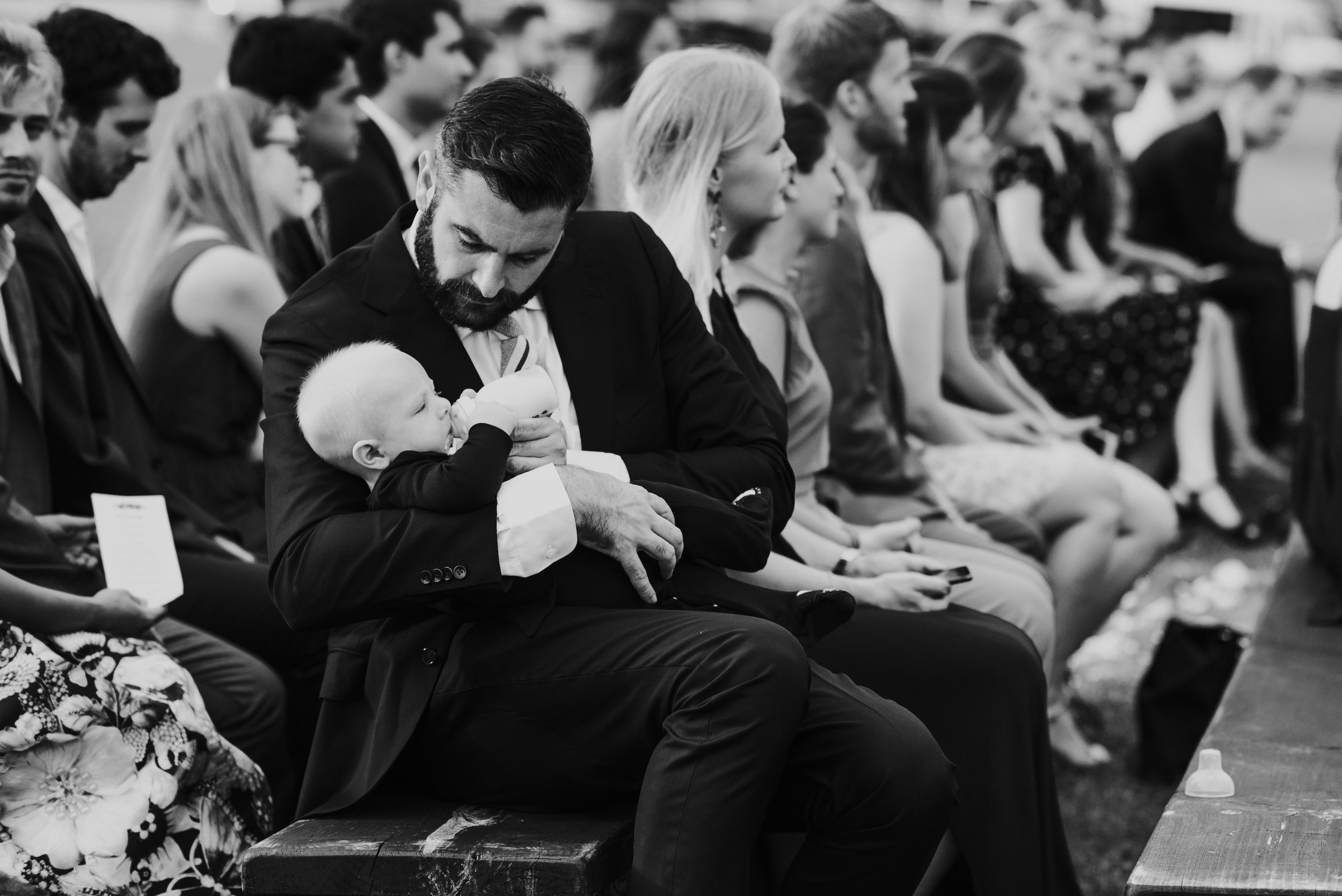 Father feeding his son during a wedding.