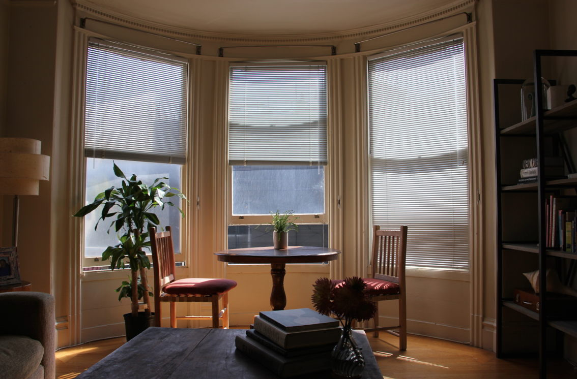 After: The round table draws attention to the bay windows by visually mimicking the curved shape without blocking their precious source of natural light.