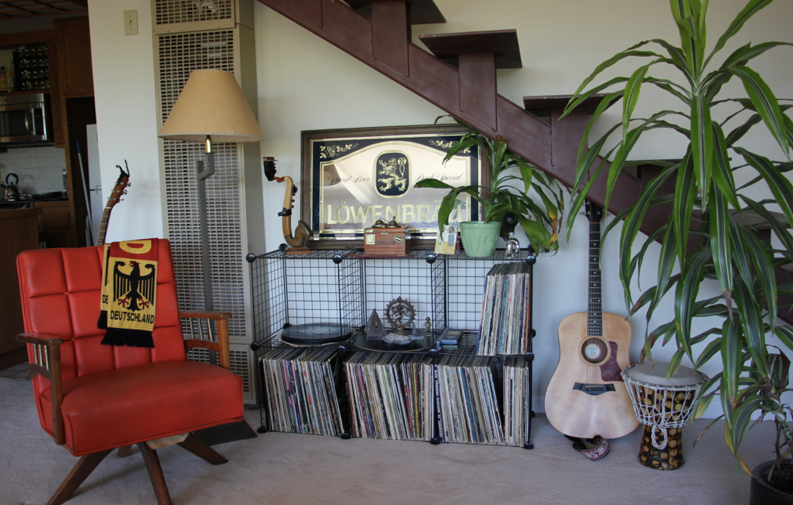 After: The orange chair provides a more proportional seating option, better access to Greg's musical instruments and records, as well as adding a pop of visual interest to the room.