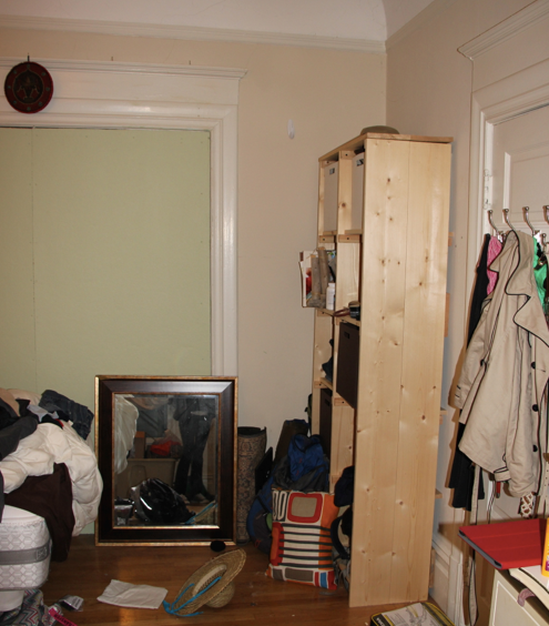 Before: The green double doors draw unwanted attention to the makeshift status of this former living room.