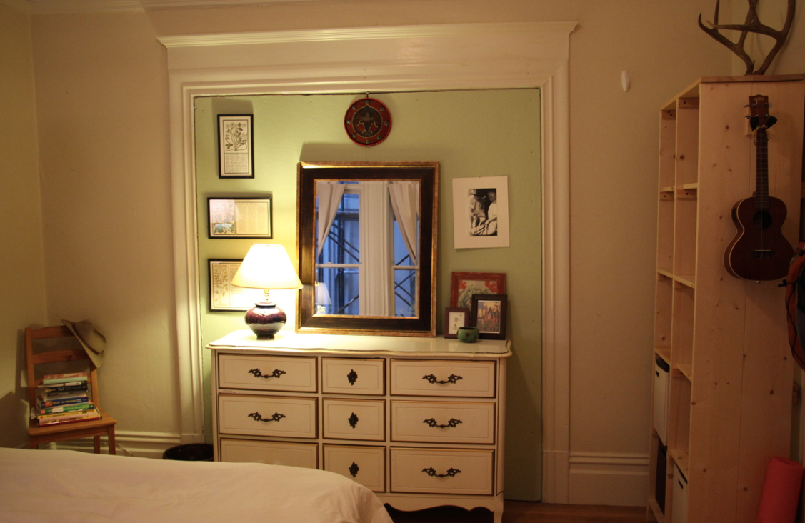 After: By setting the dresser within the door frame, the green doors and molding take on a feeling of an intentional accent wall and architectural framing element.