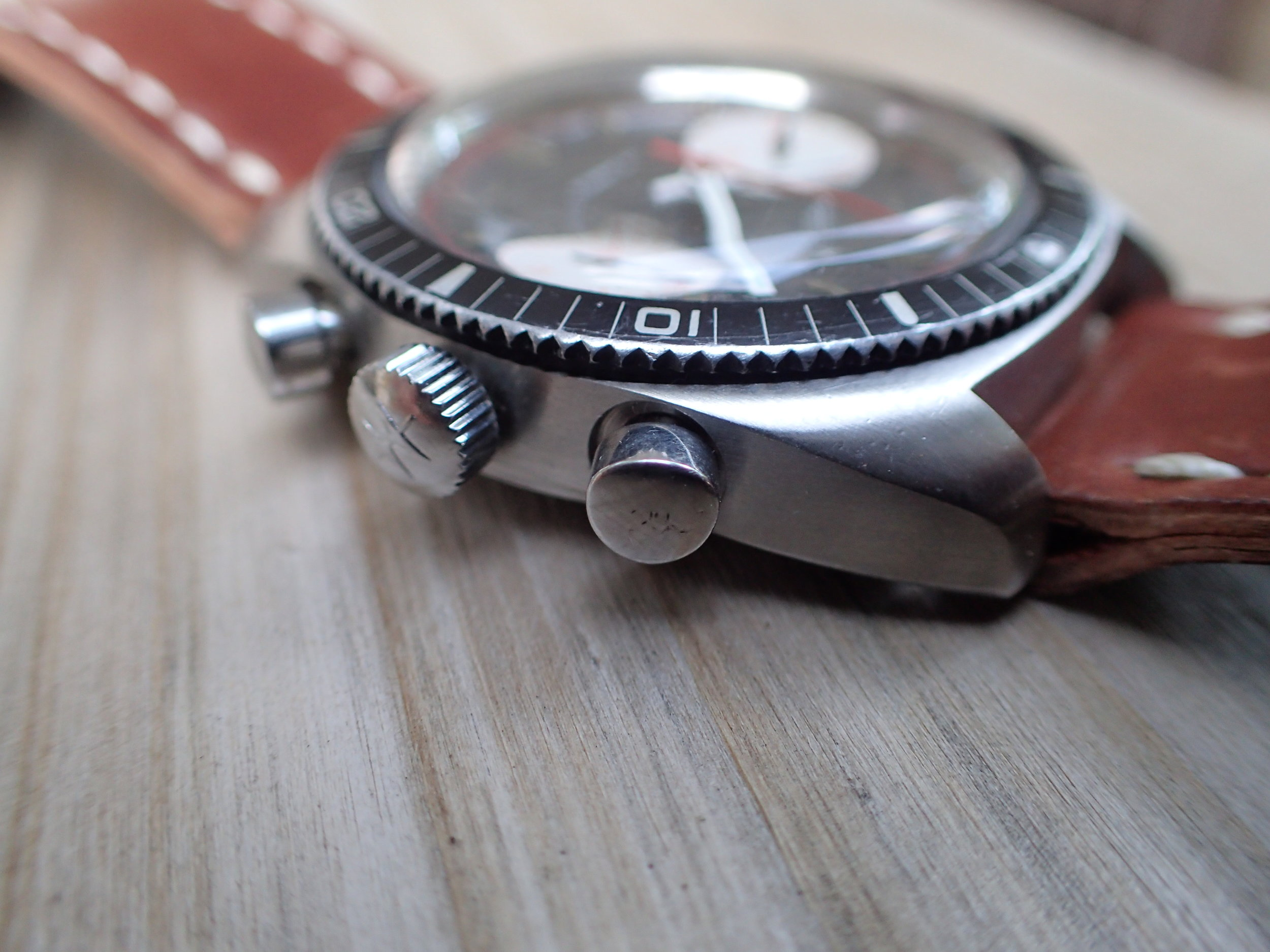 Seen here, the softly triangular shape of the pushers and signed crown of the Chrono-Diver.