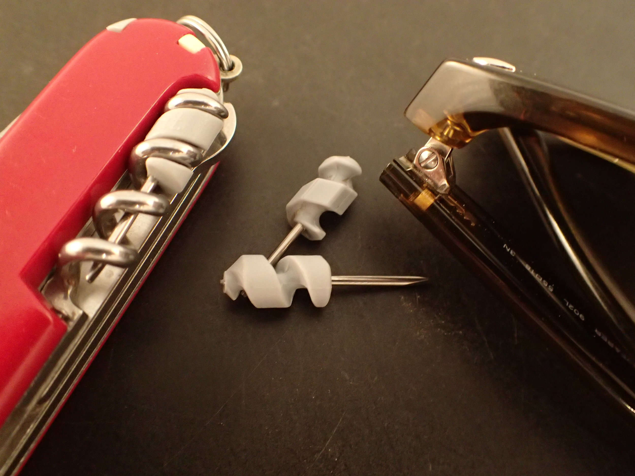 The fine screwdriver in older (smooth, round) and current (faceted) form. Also seen stored in the corkscrew of the Compact.