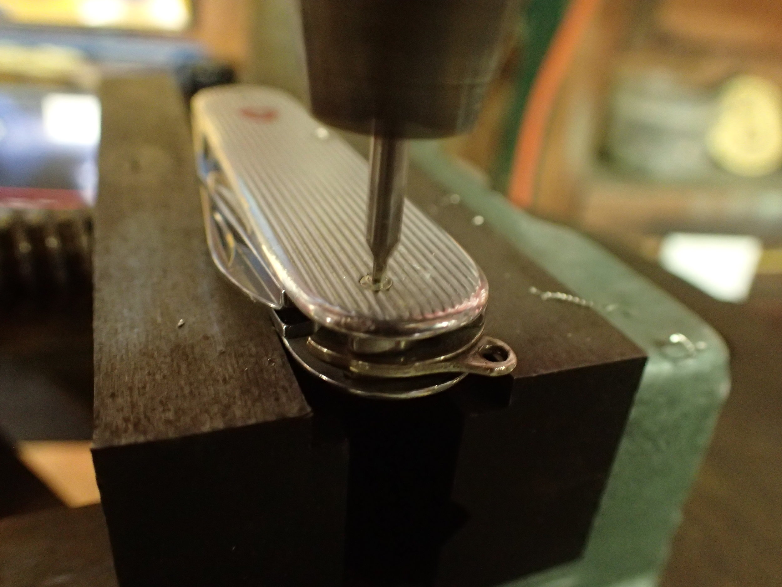 The rivet heads on the pins of the subject knife being drilled out.