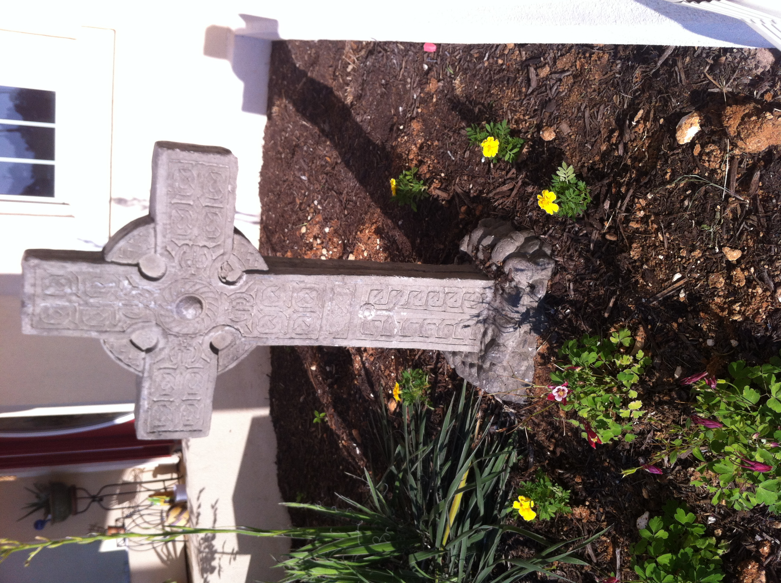 Clara planted Easter flowers around the cross by our front door.
