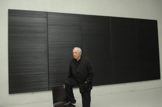 Pierre Soulages in front of one of his paintings