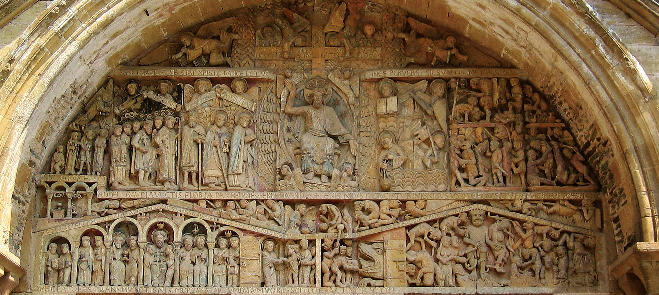 """The Last Judgment (Tympanum of the Church of Sainte-Foy, painted limestone relief, dated early 12th century, shortly after 1107) In the centre of the middle register a mandorla encloses the enthroned Christ. Compare Revelation 4:3, """"there was a rainbow round about the throne."""" Two angels with candles stand guard at the base of the throne. On the left the elect process to the throne: the Virgin Mary first, followed by St. Peter, then Dadon, the hermit who established the first oratory in Conques, a few meters away from this tympanum."""