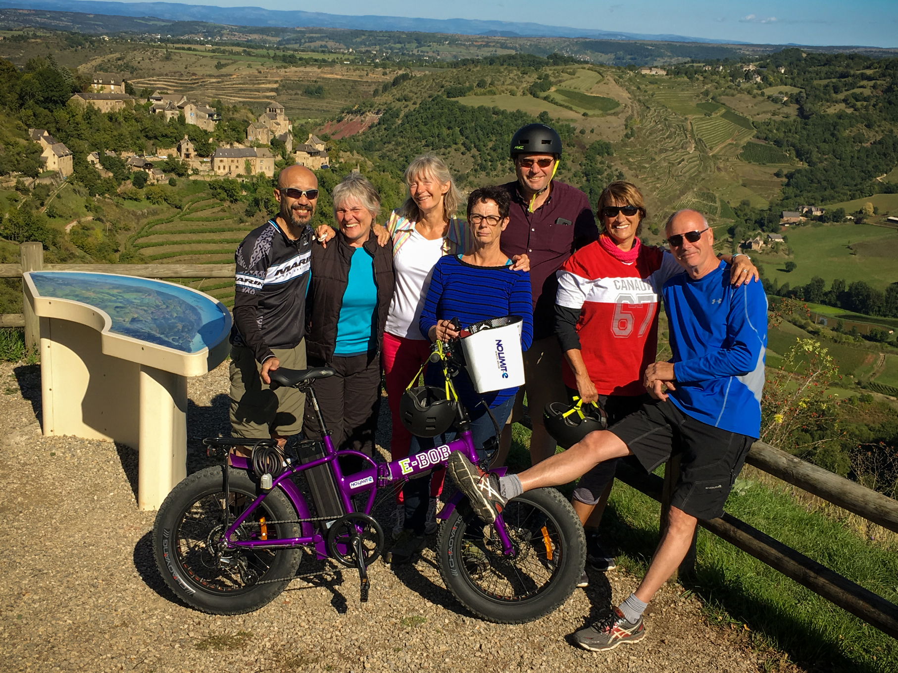 From left to right, Jack, Nadine, Véronique, Laura, Dan, Debbie and Ernie during their biking day in Aveyron in front of Cassagnes-Comtaux and the Marcillac vineyards.
