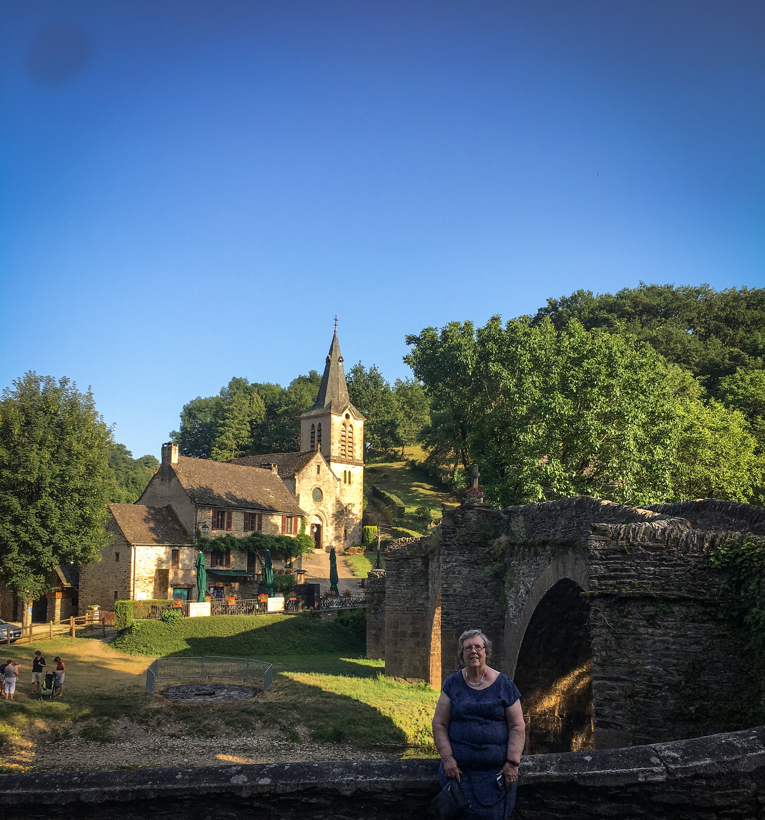 Carol trying to stay in the cool by the Aveyron river, the old cobblestone bridge leading to the church, a few houses, a caf é  and its welcoming terrace. It was a very hot day when visiting Belcastel village and its marvelous medieval château.