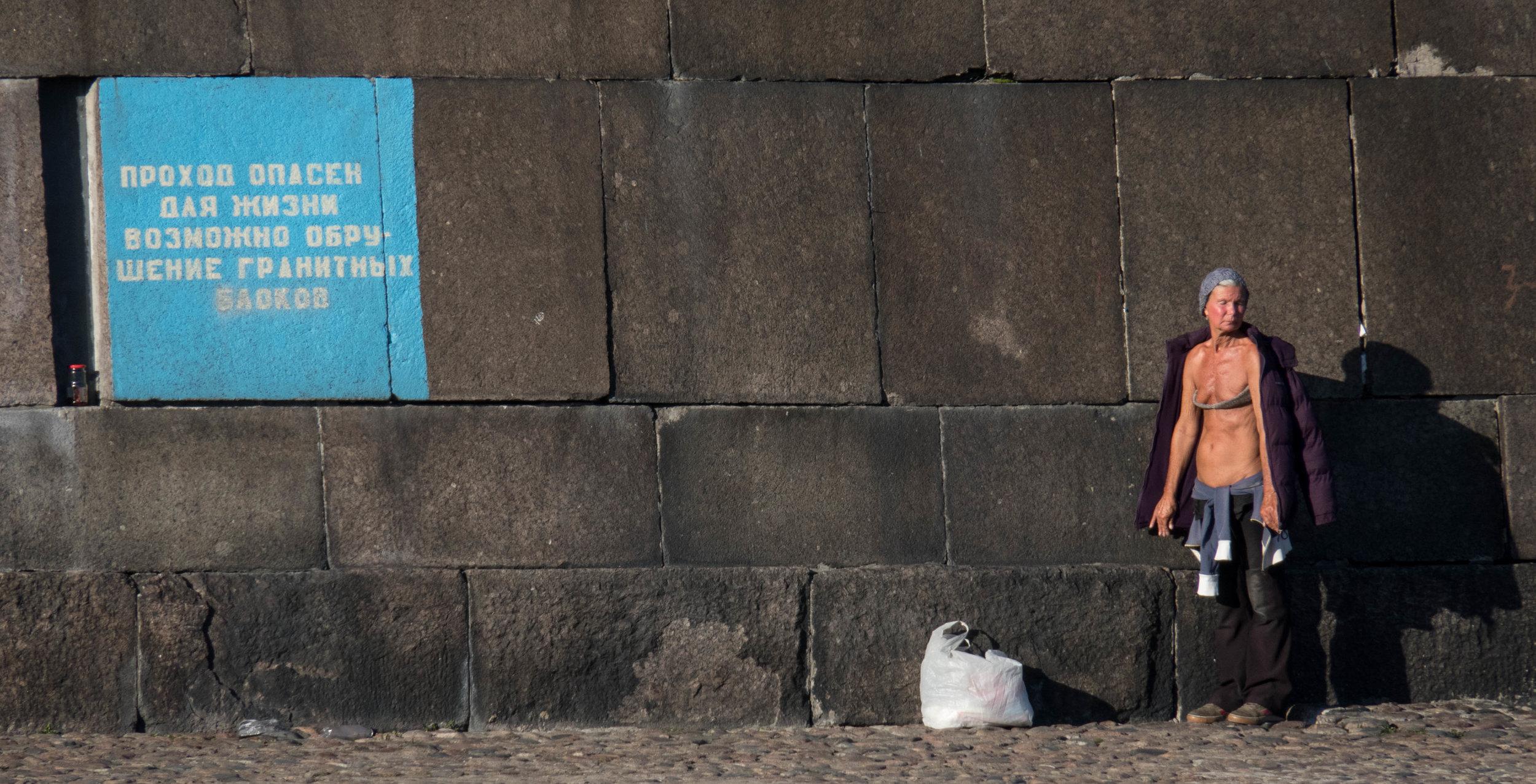 Zonnebaden bij +4 (of -4)is op dit plekje onder muur van de Petrus-en-Paulusvesting niet ongebruikelijk. Het opschrift links waarschuwt voor vallende granietblokken.