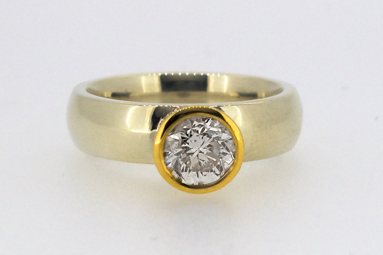 1 carat diamond rubover set in 18 carat yellow gold, on a 9 carat white gold band