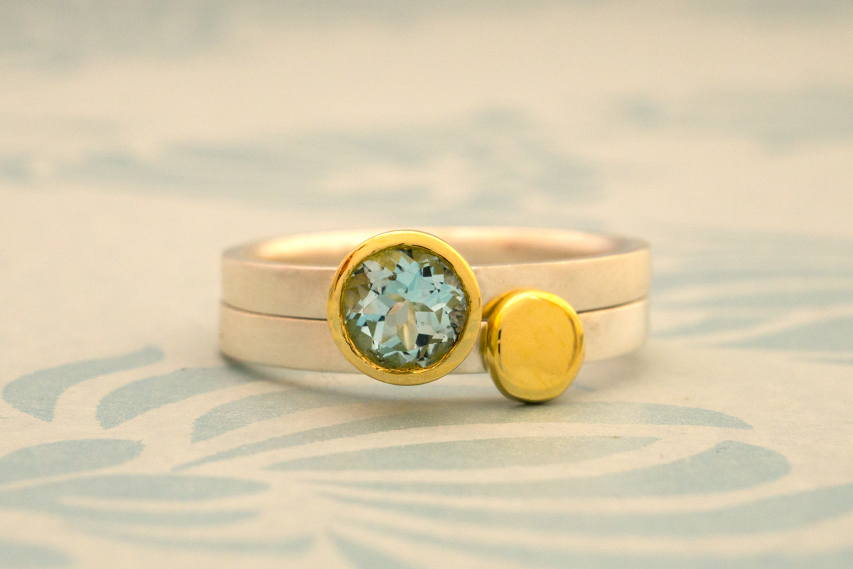 Sky blue topaz set in 18 carat gold and 18 carat gold nugget stacking rings
