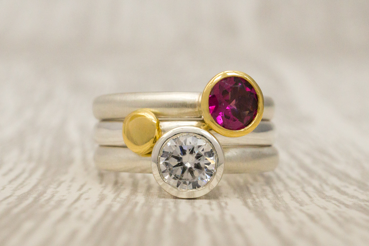 Stacking rings trio: Rhodolite garnet set in 18 carat gold on a silver band; gold nugget on a silver band; and clear cubic zirconia in silver scattered trillions ring.