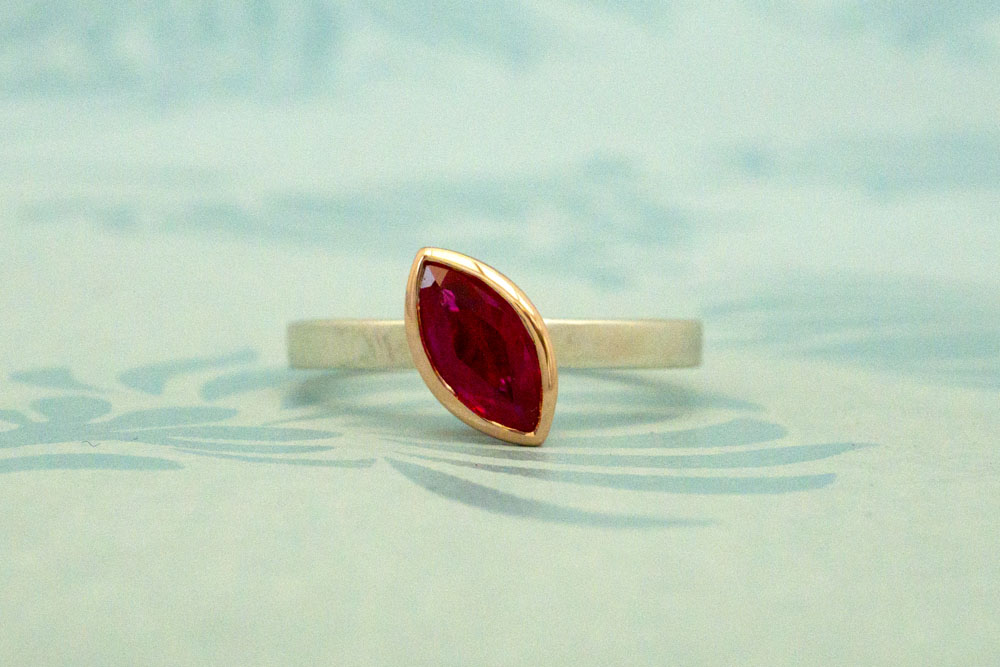 Marquise shaped ruby set in 9 carat rose gold on a silver band
