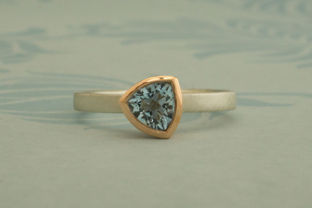 Trillion shaped aquamarine set in 9 carat rose gold on a silver band