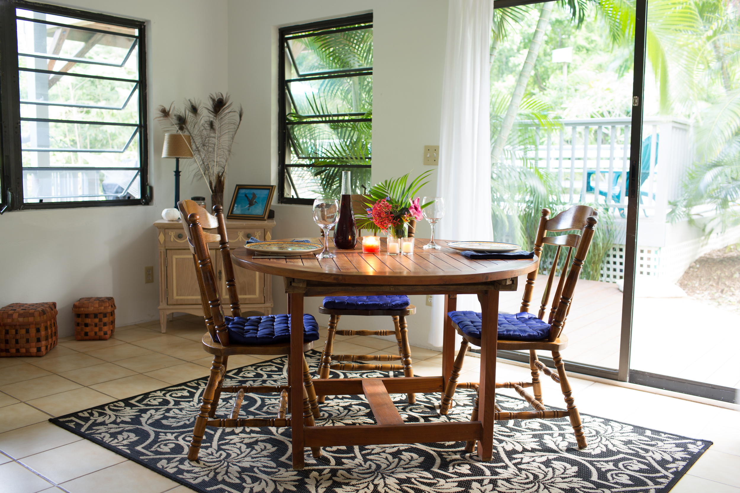 The dining table spills out to the wrap around covered deck with hammock strung poolside, gas grill and comfy shaded seating for reading