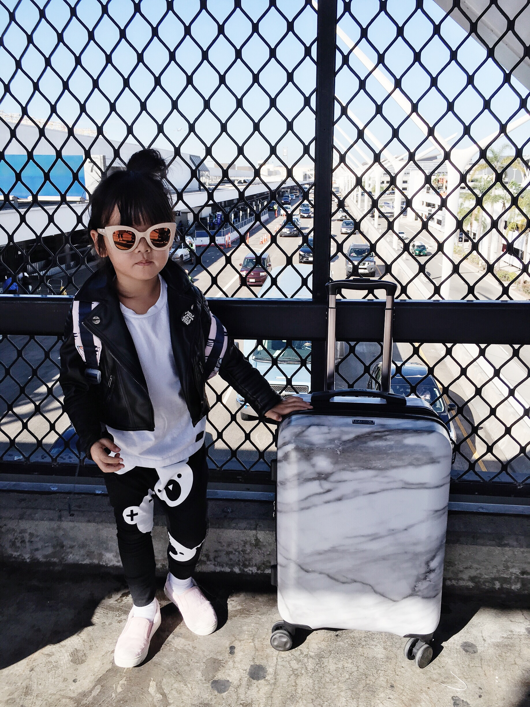 Zooey's Airport Style: Carry on Marble case:  Calpak , Sunnies:  Sons + Daughters , Vegan Leather Jacket:  Eve Jnr , Tee:  Minixstyle , Pants:  Huxbaby , Sneakers:  AKID  (easy to take off on the plane!)