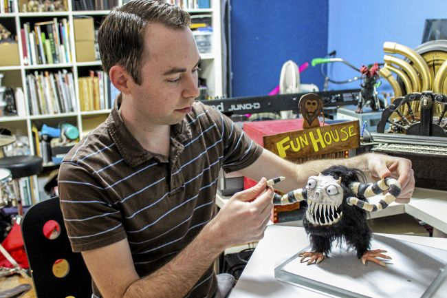 "Josh Funk, a Chico director and writer, demonstrates how his puppet will be used in creating his live action and stop-motion film, ""The Spaceman."" (Leila Rodriguez —Enterprise-Record)"