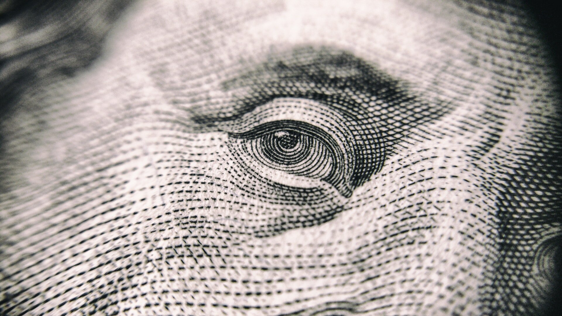 A close up of an eye from a $100 bill. Photo by Vladislav Reshetnyak from Pexels