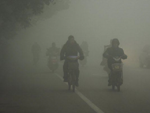 Cyclists travel on the road on a hazy day in Huaibei, Anhui province, China   Photo courtesy of : The Christian Science Monitor.
