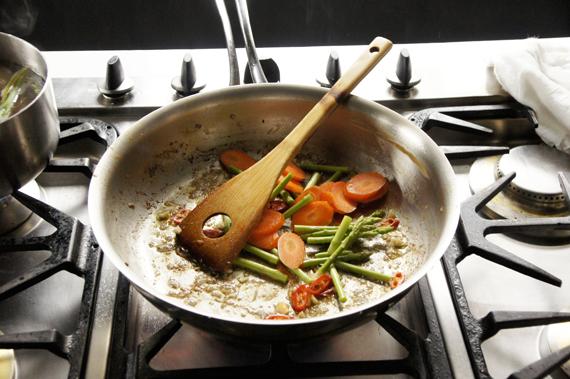 2. 用同一只鍋子,適量熱炒油再加入另一半的蒜末以大火爆香,加入辣椒炒紅蘿蔔與蘆筍。