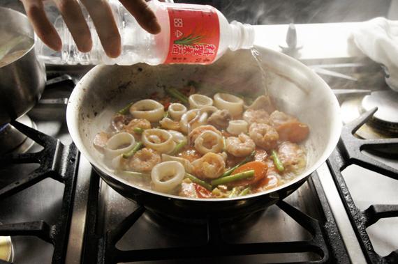 加入海鮮繼續拌炒。加入米酒,以大火將醬汁濃稠收乾。