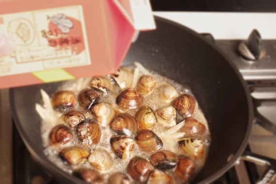 3. 加入清酒與味淋稍微拌炒,蓋鍋待蛤蜊開後再加入麻油即可。