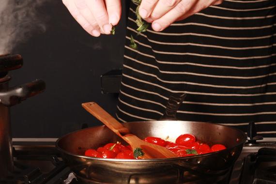 1. 輕輕用刀壓扁小蕃茄。 於平底鍋熱油並加入大蒜爆香後,放入蕃茄炒香數分鐘,再加入蘿勒葉、鹽巴和黑胡椒調味拌炒。