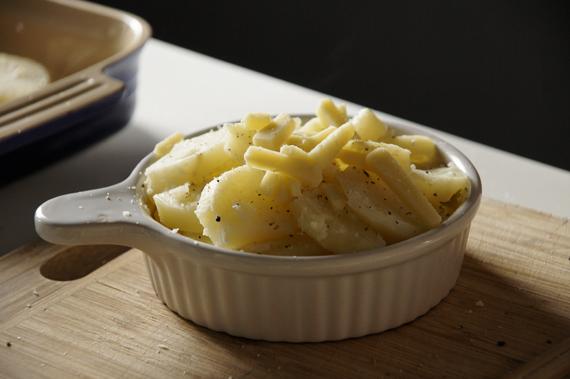 2. 將馬鈴薯取出後濾掉湯汁,在烤盤內依序疊上馬鈴薯片、鹽巴、胡椒、起司、鮮奶油,重複直到將烤盤裝滿。