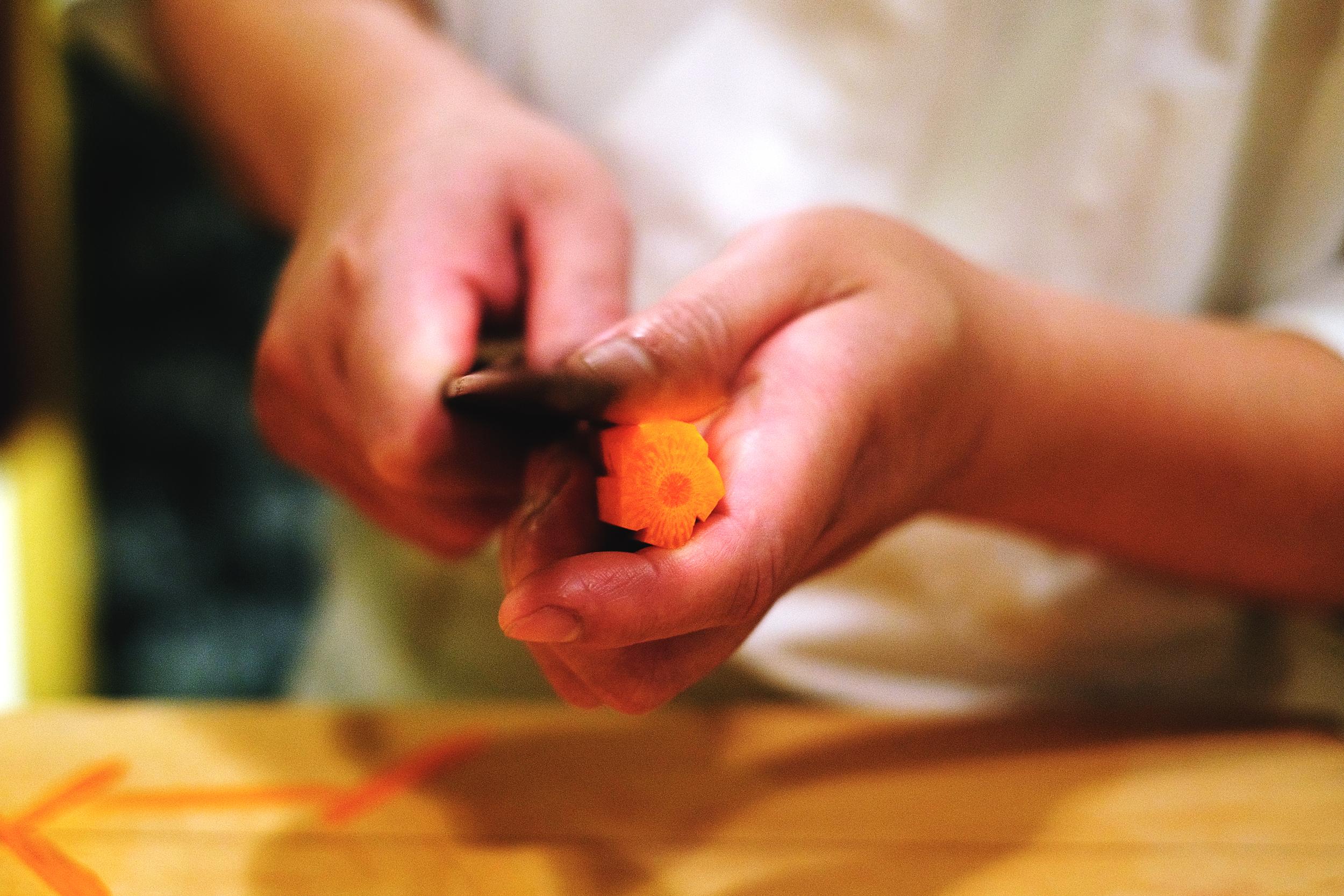 2. 在五角形的某一面,從一個尖點,微微圓弧的斜切入中心點,依序完成五個面,都完成後將紅蘿蔔轉向,重複同樣動作,即完成