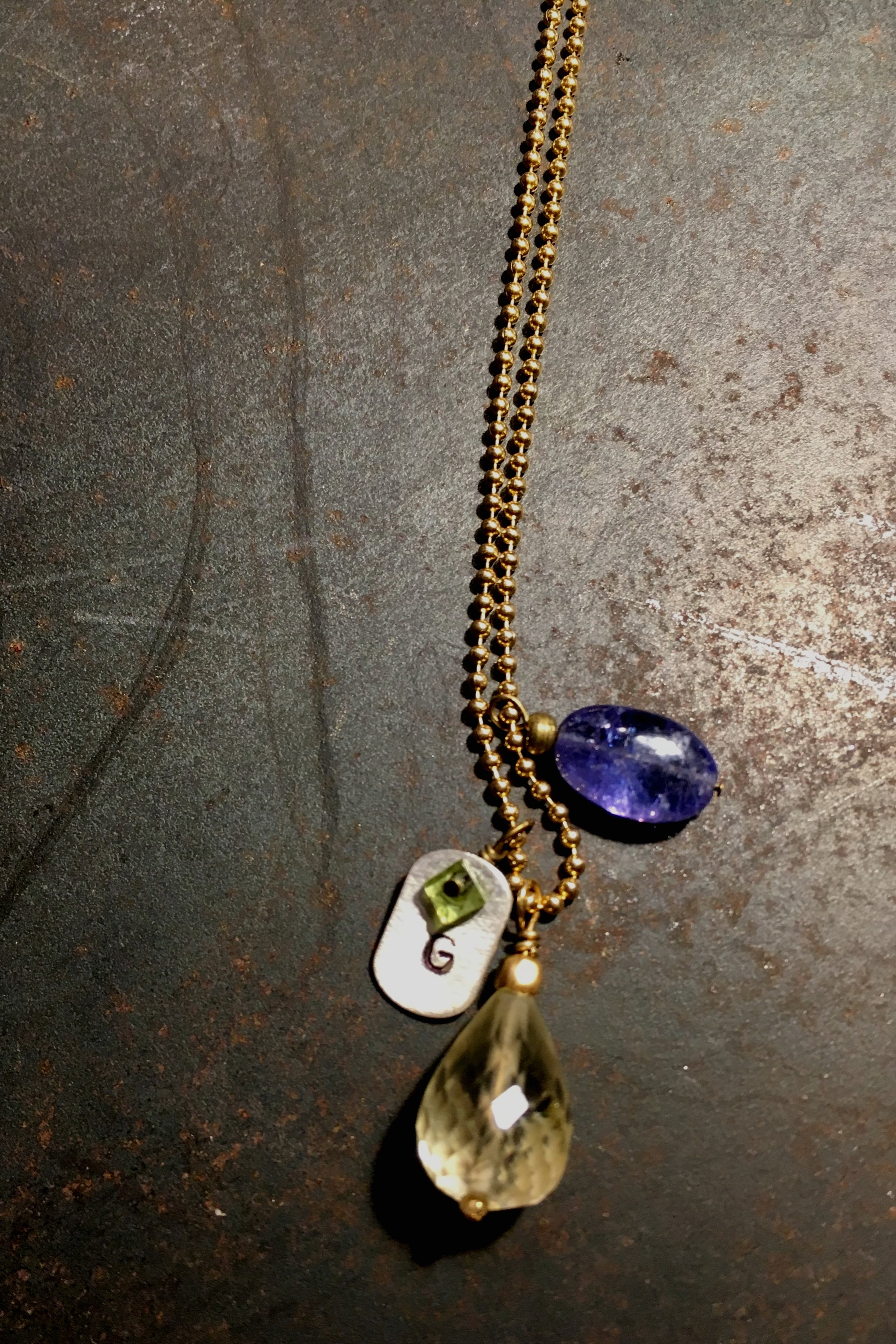 Gita chose a  citrine  drop and  tanzanite  — believed to increase  clarity  and foster  emotional balance , respectively — to accompany a gold ball chain and silver tag with her initial. I added the  peridot  square for  healthy body and relationships .  I hope her AMULET by D brings her good luck and happiness.