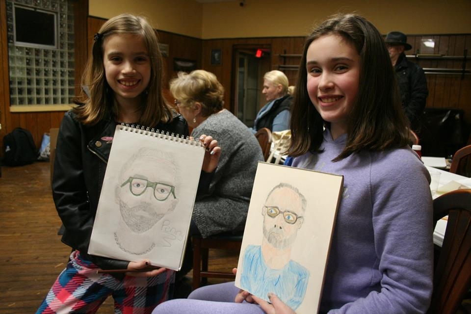 Penny and Tillie Averre showing off their drawings of Alan Glazen at Sachsenheim Hall.  12-14-18