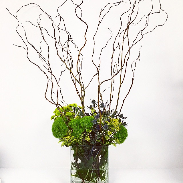 @interfaceamericas is having an event today and #mrsdovebelly provided all of the floral...here is just one of the many! #floral #interface #design #arrangement #event #flowers #branches #green #yellow #purple #client