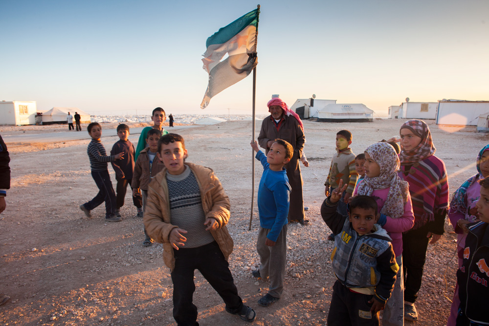 A young boy flies the Syrian opposition flag in Zaatari refugee camp.