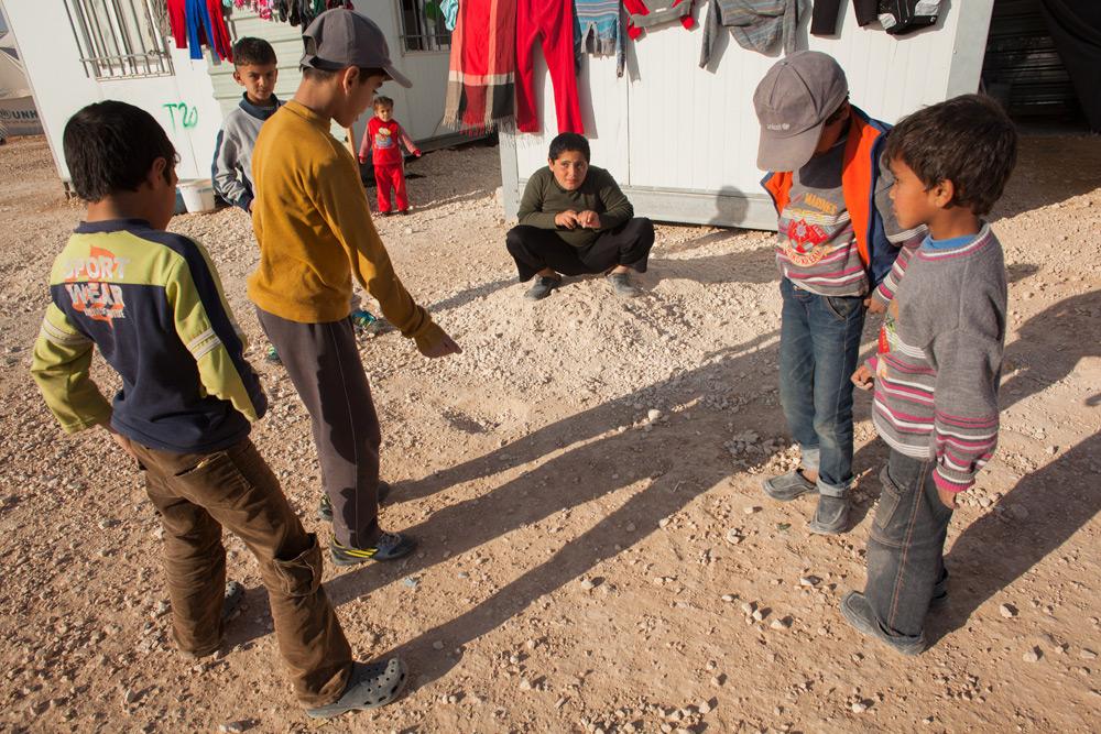 Syrian boys play marbles in the sand at Zaatari.